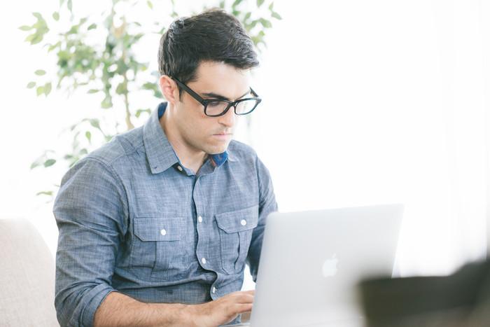 男性がPCの前に座って作業している